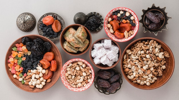 An elevated view of traditional sweets; dried fruits and nuts on white background