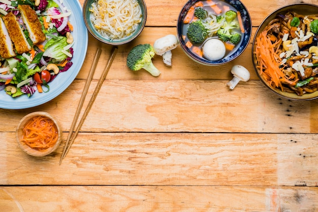 An elevated view of traditional thai food with chopsticks on wooden desk