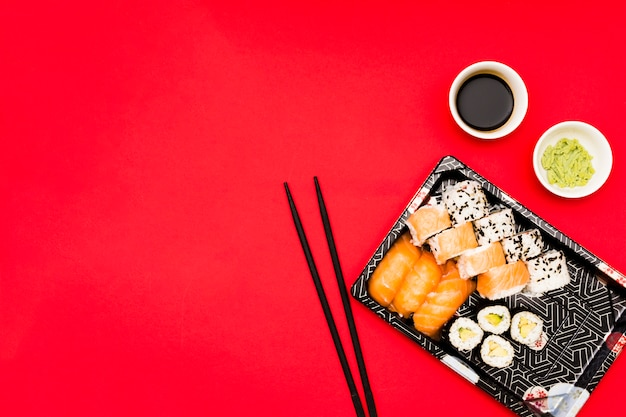 An elevated view of tray filled with tasty rolls near wasabi and soy sauce in bowl on red surface