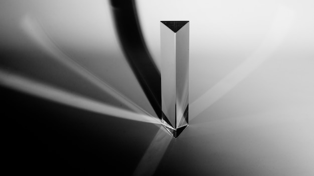 An elevated view of triangle prism with dark shadow on grey background