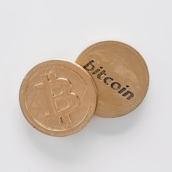 Elevated view of two bitcoins over the white background
