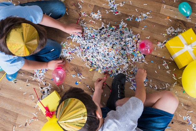 Elevated view of two boys gathering confetti on wooden floor