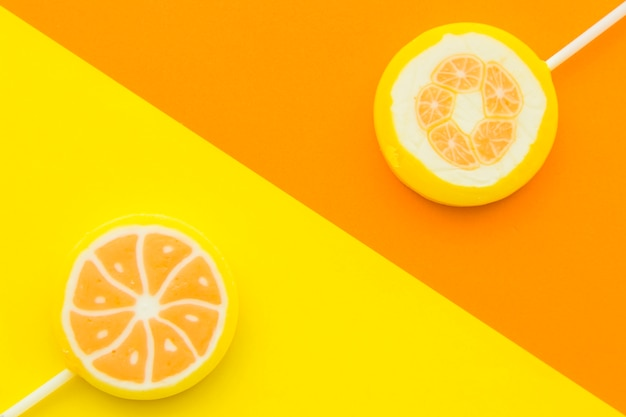 Elevated view of two citrus fruit lollipops opposite each other on multi colored background