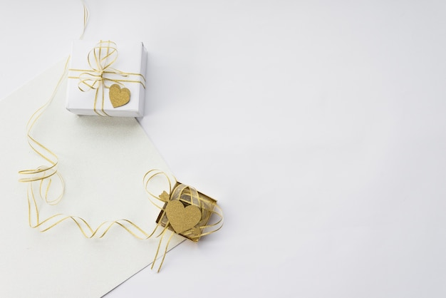 Elevated view of two gift box with blank paper on white backdrop