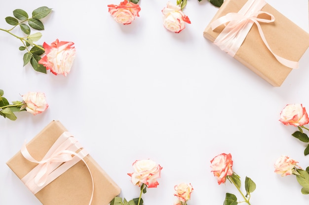 Elevated view of two gift boxes and roses on white backdrop