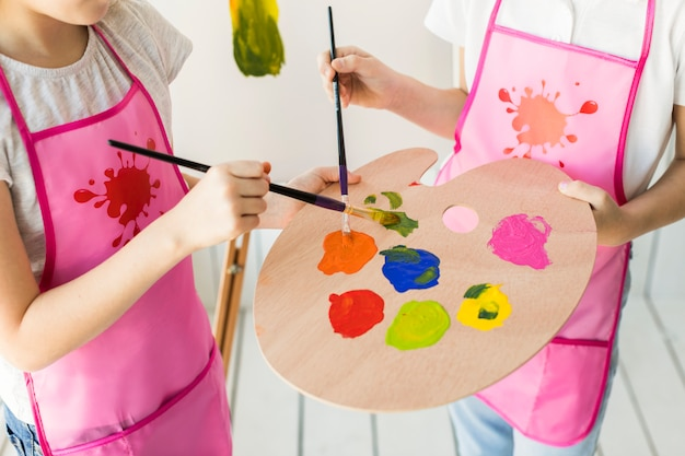 An elevated view of two girls in same pink apron mixing the paint on wooden palette with paint brush