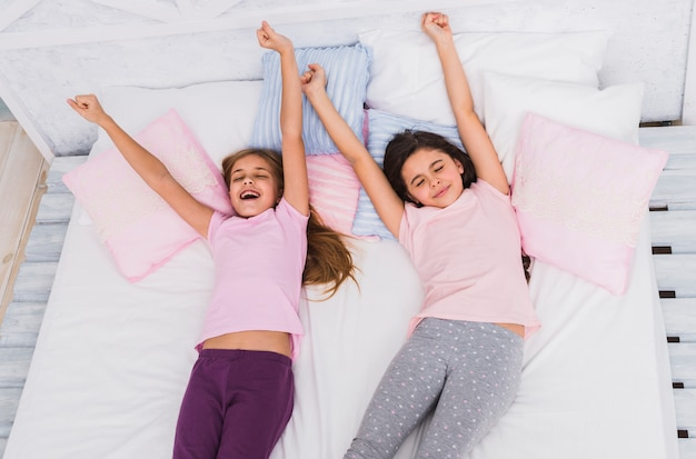 An elevated view of two girls stretching their arms while waking up on bed