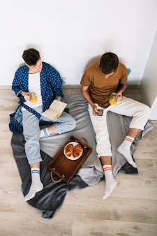 Elevated view of two man reading books holding juice of jar