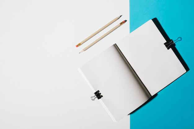 Elevated view of two pencils and open notebook attach with bulldog clip