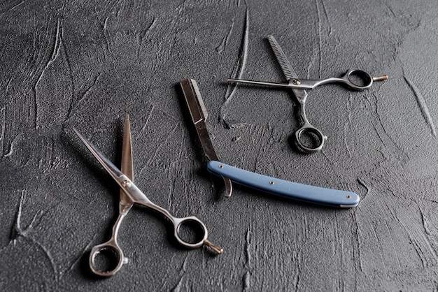 Elevated view of two scissors and razor on black background