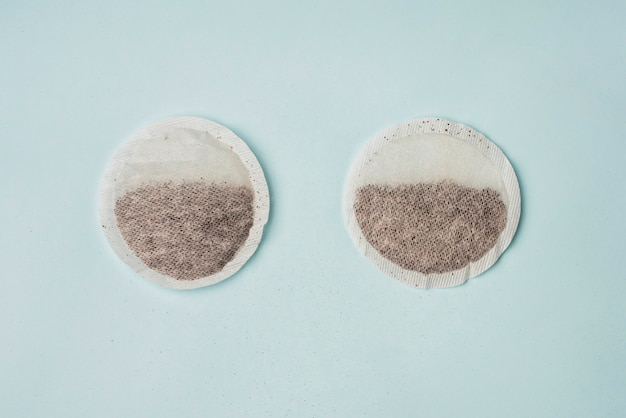 Elevated view of two tea bags on blue backdrop