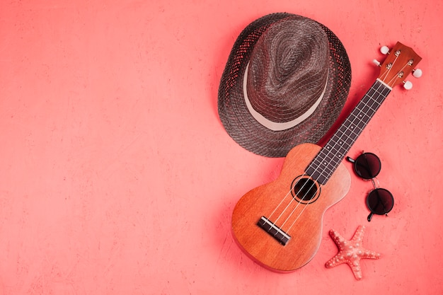An elevated view of ukulele; sunglasses; starfish and hat on coral background