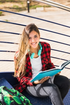 An elevated view of university student sitting on staircase holding book in hand
