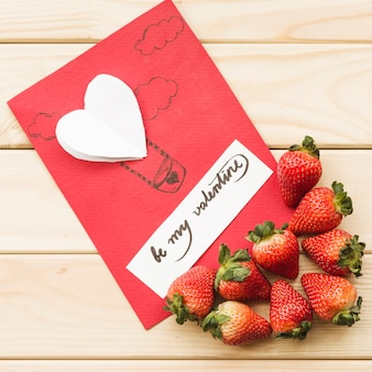 Elevated view of valentine day card with strawberries on wooden background