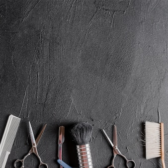 Elevated view of various barber tools on black background