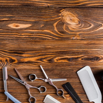 Elevated view of various barber tools over wooden background