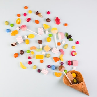 Elevated view of various candies with ice cream waffle cone on white background