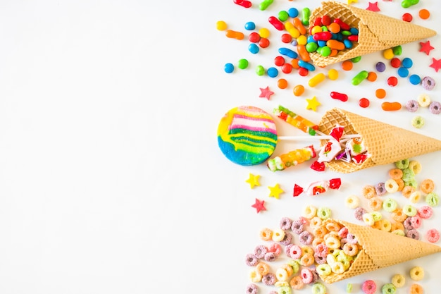 Elevated view of various colorful candies with waffle ice cream cone on white surface