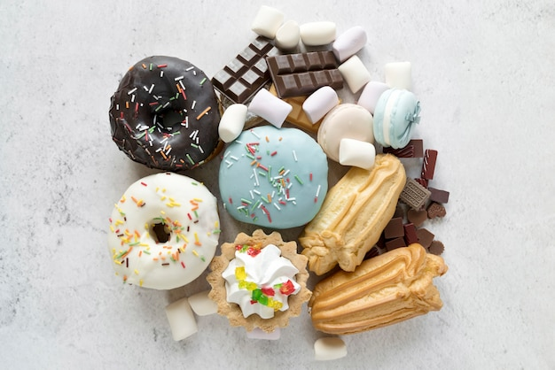 Elevated view of various confectionery food on white cement textured backdrop