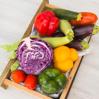 Elevated view of various fresh vegetables in wooden container