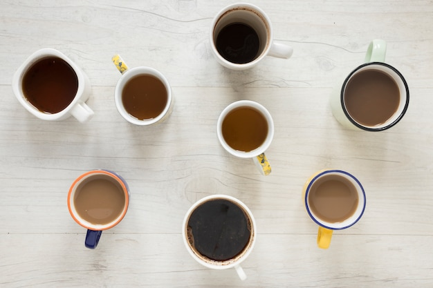 Elevated view of various kinds of coffee in cups on desk