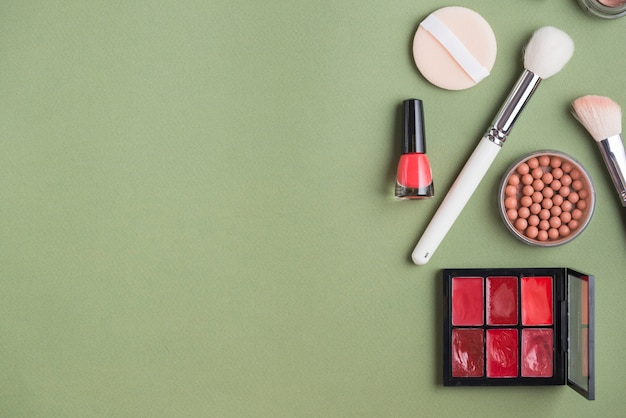 Elevated view of various makeup products on green background