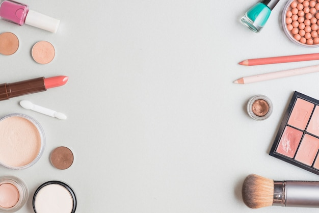 Elevated view of various makeup products on white background