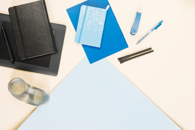 Elevated view of various stationeries on colorful paper background