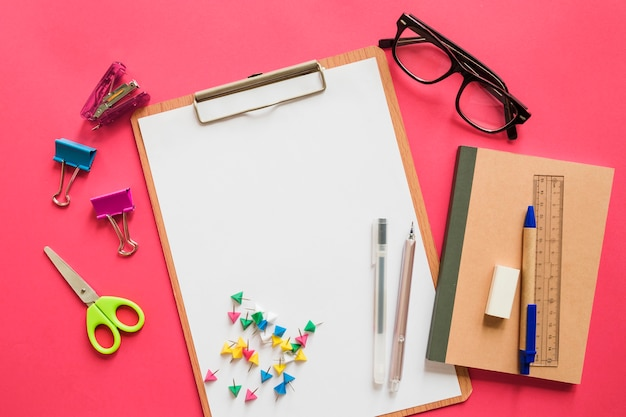 Elevated view of various stationeries on pink background