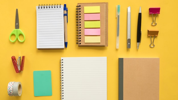Elevated view of various stationeries on yellow backdrop