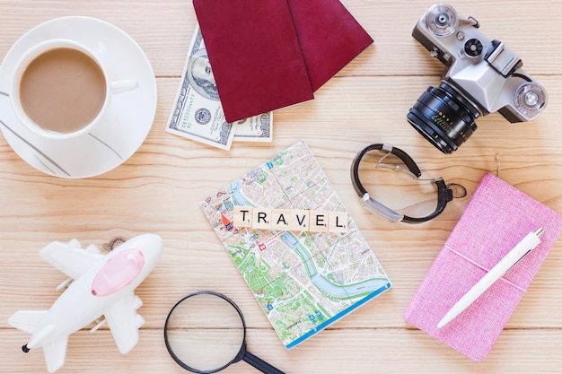 Elevated view of various traveler accessories with tea cup on wooden surface