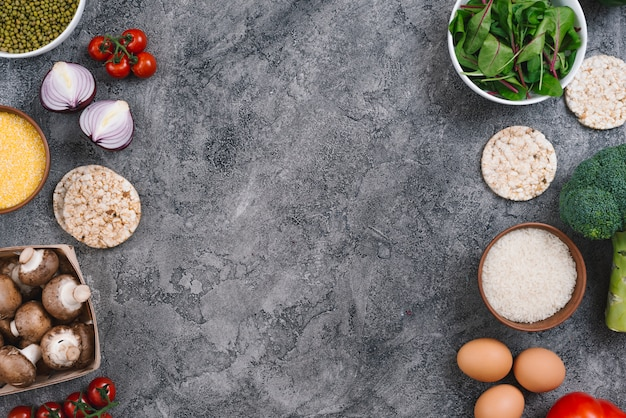 An elevated view of vegetables; eggs and puffed rice cake on gray concrete backdrop