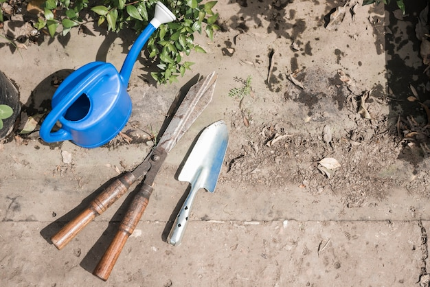 Elevated view of watering can; hand shovel and gardening scissors in greenhouse