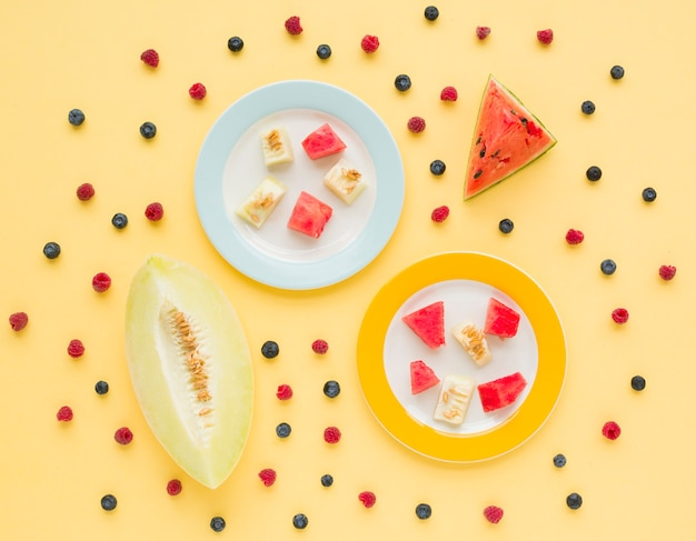An elevated view of watermelon and muskmelon with blueberries and raspberries on yellow background