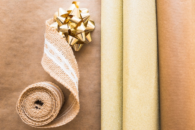 Elevated view of weaving ribbon and golden bow with gift paper on brown paper