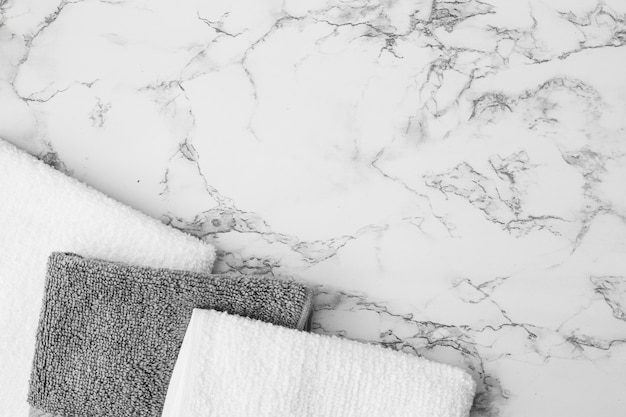 Elevated view of white and black towels on marble background