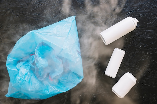 Elevated view of white bottles and plastic bag surrounded by smoke
