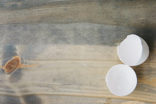 Elevated view of white broken egg shell on wooden background