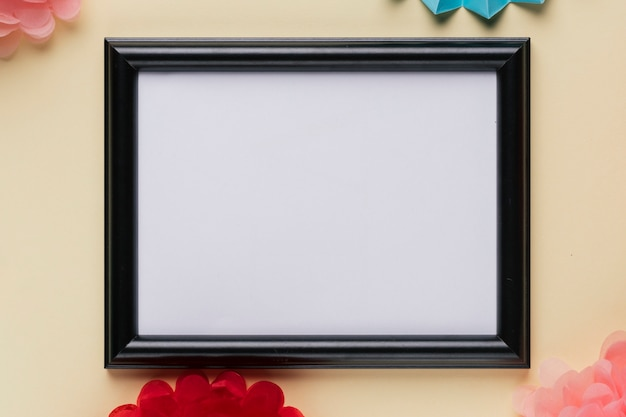 Elevated view of white empty frame on beige backdrop