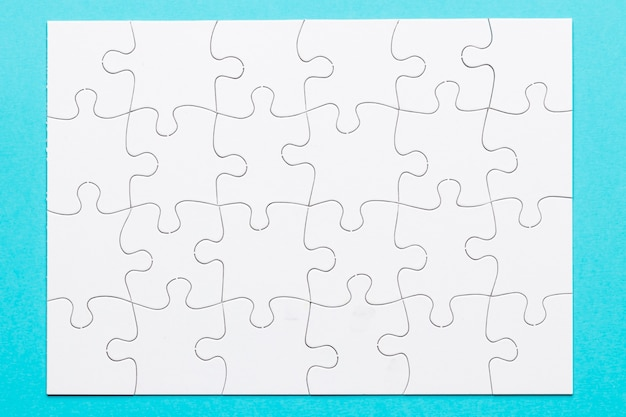 Elevated view of white jigsaw puzzle grid on blue surface