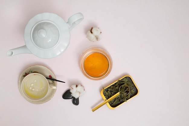 An elevated view of white teapot; honey; cotton; leaves and la stone against white background