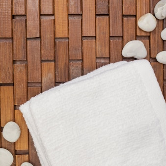 Elevated view of white towel and pebbles on wooden floor