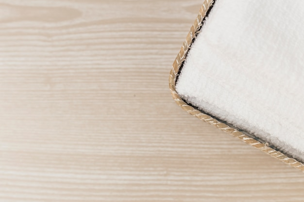 Elevated view of white towel in tray on wooden backdrop