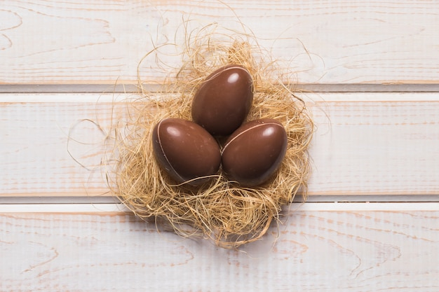 An elevated view of whole chocolate easter eggs in the nest on wooden desk