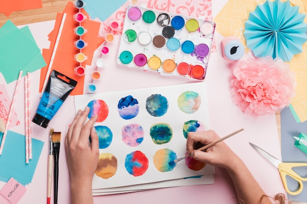 Elevated view of woman hand painting colorful abstract circle on white paper