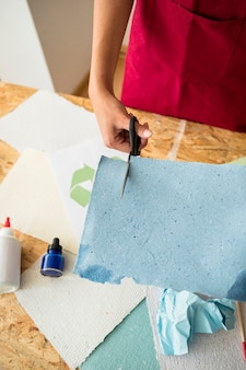 Elevated view of woman's hand cutting blue paper with scissors