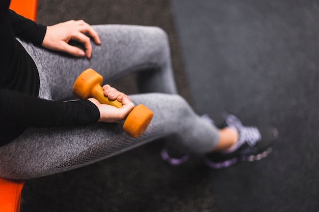 Elevated view of a woman's hand exercising with dumbbell