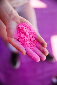 An elevated view of woman's hand holding pink holi color