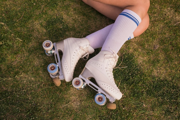 An elevated view of woman's leg wearing white vintage roller skate lying on green grass