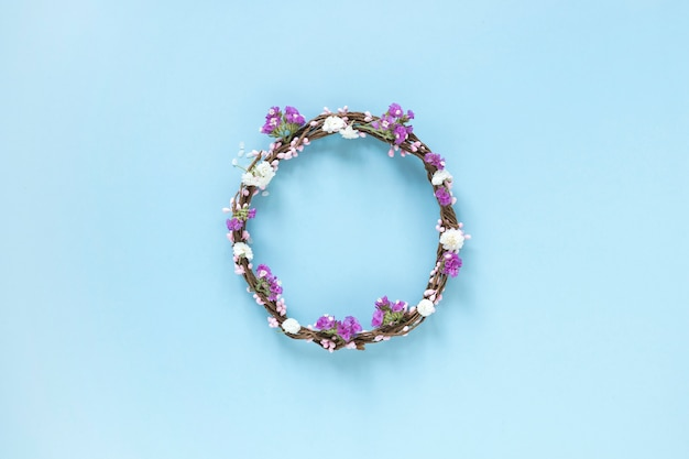 Elevated view of wreath made up of flowers on blue backdrop